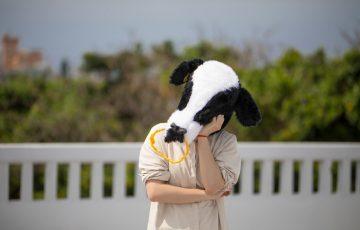 牛のマスクを被り首を傾げる人