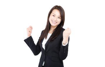 笑顔でガッツポーズをするスーツ姿の女性