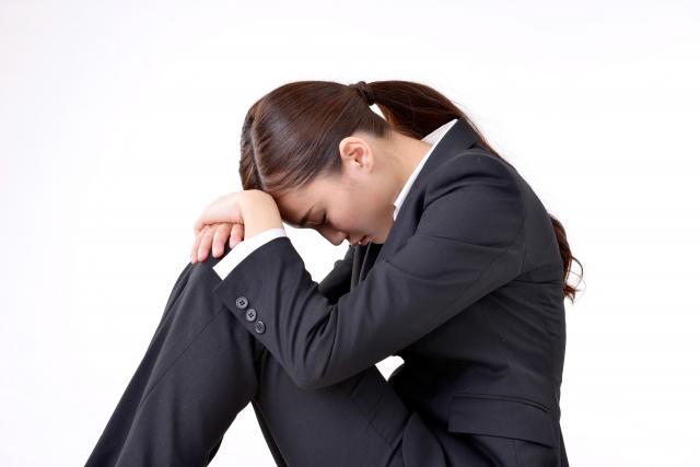 三角座りで項垂れるスーツ姿の女性