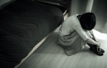 ベッドの側でうつむく女性