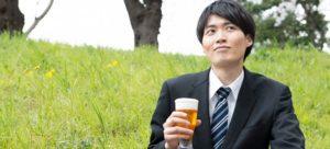 ビールを右手に持つスーツ姿の青年