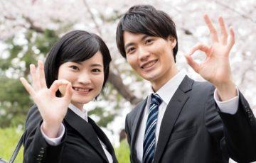 桜の木の下ではにかむスーツ姿の男女