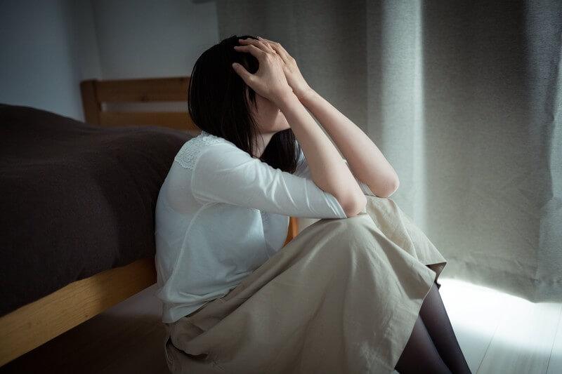 ベッドの側で頭を抱える女性
