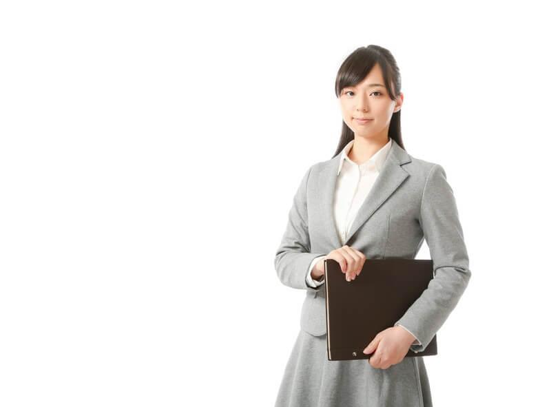 バインダーを抱えるスーツ姿の女性