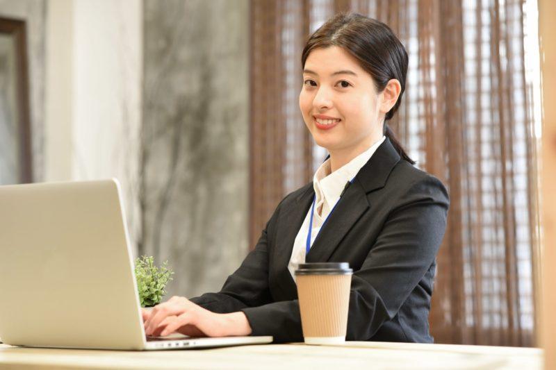 ノートパソコンに向かうスーツ姿の女性